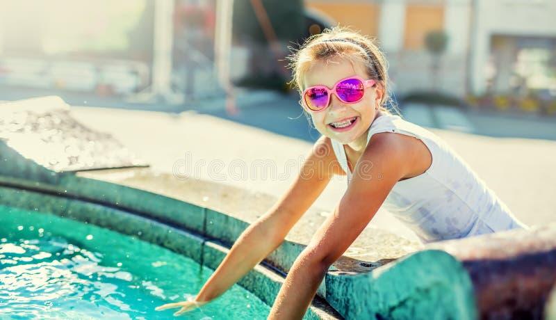 Varm dag för sommar Gullig liten flicka som spelar med springbrunnen varmt väder arkivbilder