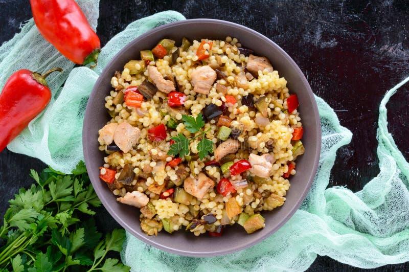 Varm diet-sallad från den bakad grönsakzucchinin, söt peppar, aubergine, löken, höna och couscous fotografering för bildbyråer