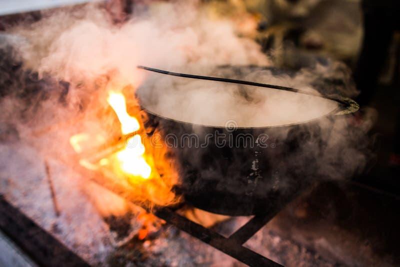 Varm gluhwein eller funderat vin i en kittel på mässan, lokal fest, varmt och kryddigt En varm hälsosam traditionell citrus drink arkivfoto