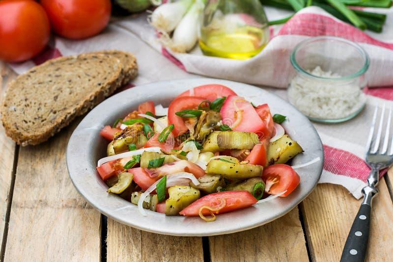 Varm höstsallad med aubergine, tomat, lök royaltyfria bilder