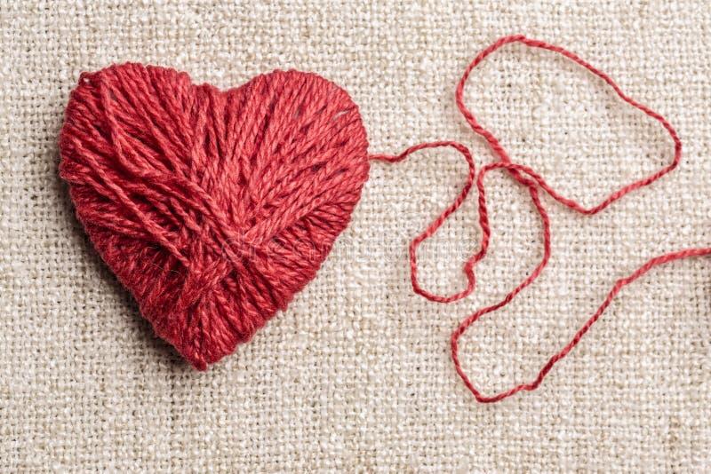 Varm hjärta som göras av rött ullgarn arkivbilder