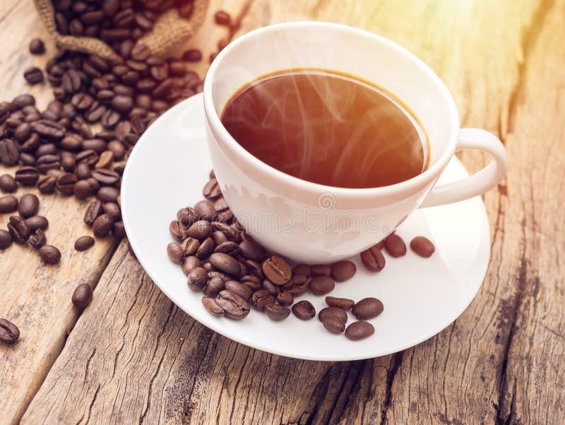 Varm kaffekopp med kaffebönan på trätabellen kaffe bg fotografering för bildbyråer