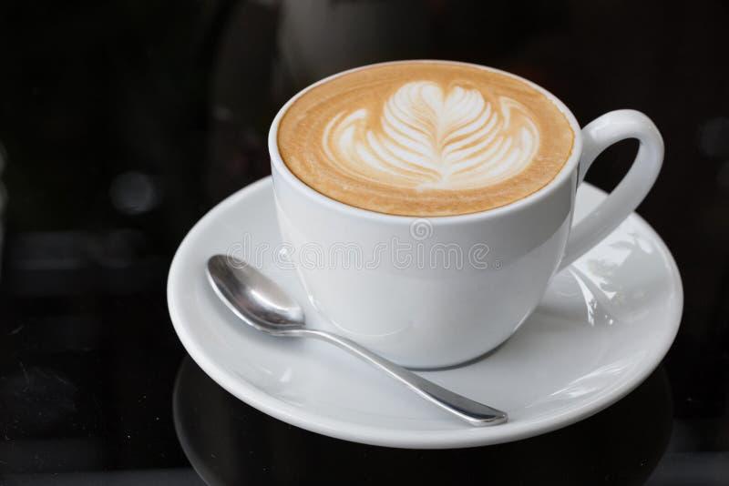 Varm kaffelatte, lattekonst med hjärta i en vit kopp arkivbilder