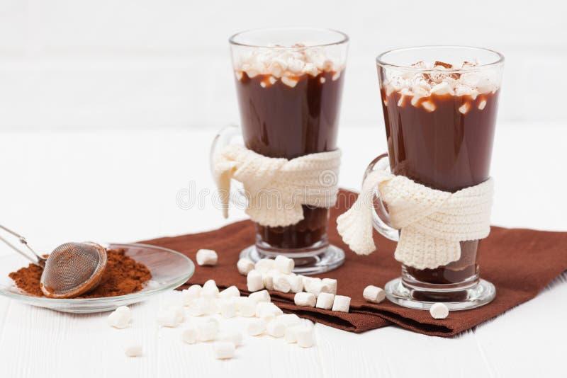 Varm kakao i exponeringsglas med marshmallow-, crocahetgarnering-, brunt- och beigaservetter på vit träbakgrund varm choklad S arkivbilder