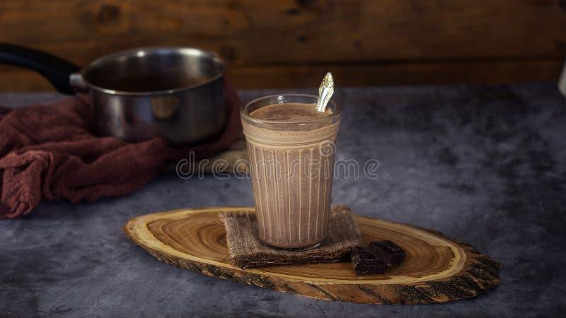 Varm kakaodrinkchoklad mjölkar i ett exponeringsglas på en träyttersida royaltyfri bild