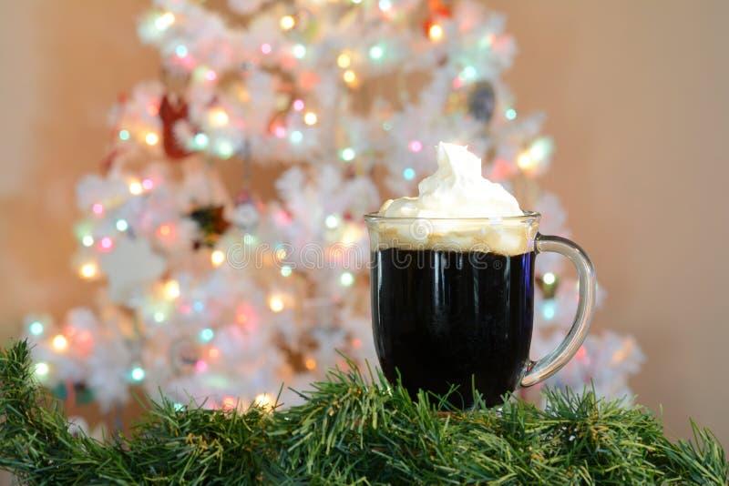 Varm kakaokopp som framme poseras av den vita julgranen med kulöra ljus royaltyfri foto