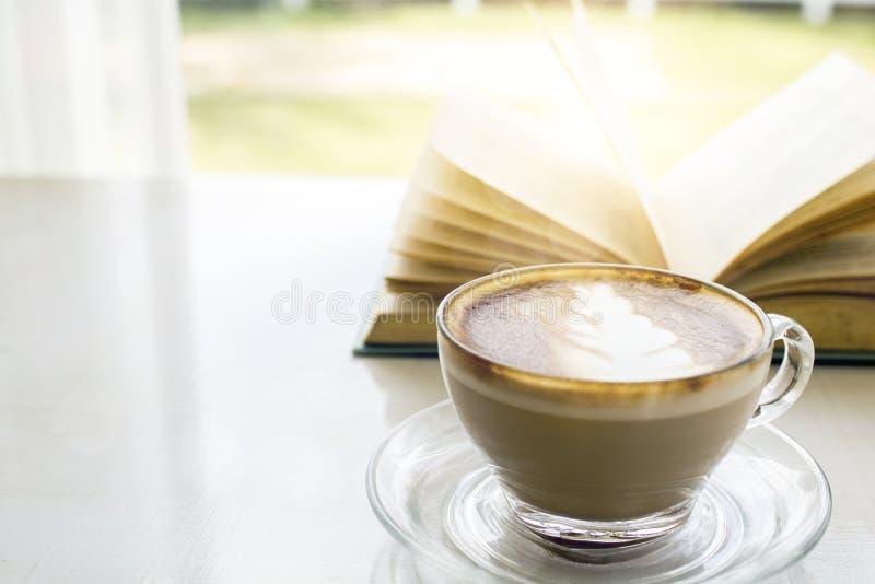 varm kopp kaffe med boken på balkong av fönstret utanför med gr arkivbild
