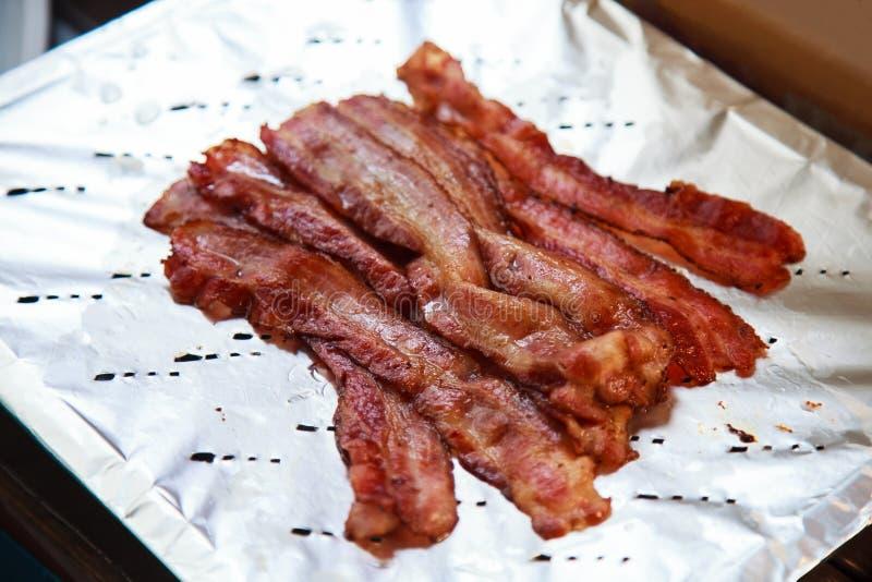 Varm läcker nytt lagad mat grillad grisköttbacon som är klar att äta på aluminum folie Sund och hurtig olja stekte köttrich med f royaltyfria foton
