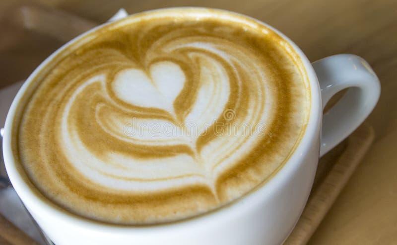 Varm Lattekaffekonst i den vita koppen royaltyfria bilder