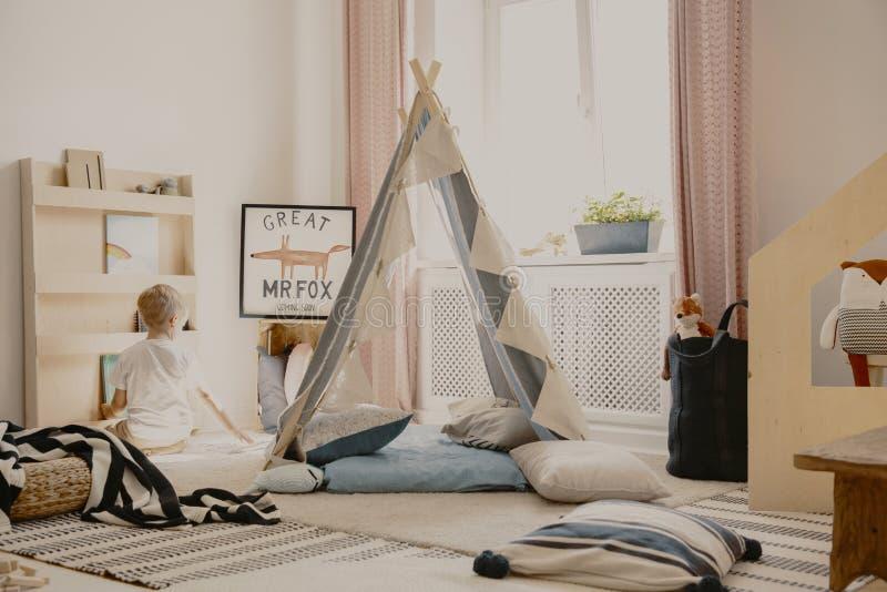 Varm och hemtrevlig scandinavian lekrum med tältet, kuddar och leksaker, verkligt foto arkivbilder