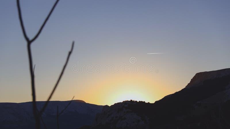 Varm och matte solnedgång på en stenig kulle arkivfoto