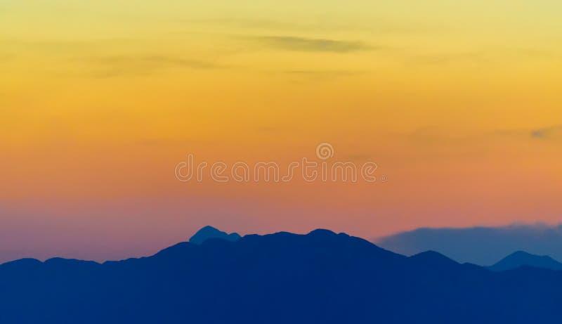 Varm orange solnedgång ovanför det blåa berget royaltyfria foton