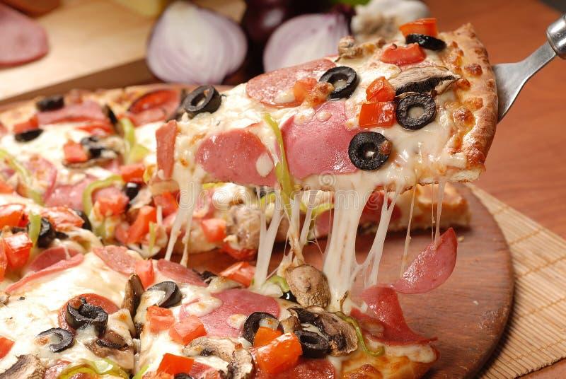 Varm pizzaskiva med sm?ltande ost p? en lantlig tr?tabell arkivbilder