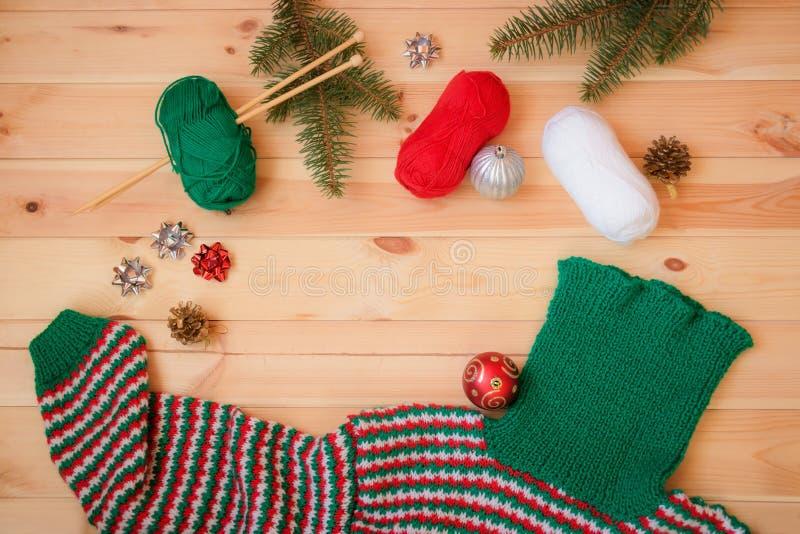 Varm röda, gröna och vita hemlagade stack tröja, granfilialer och julbollar arkivfoton