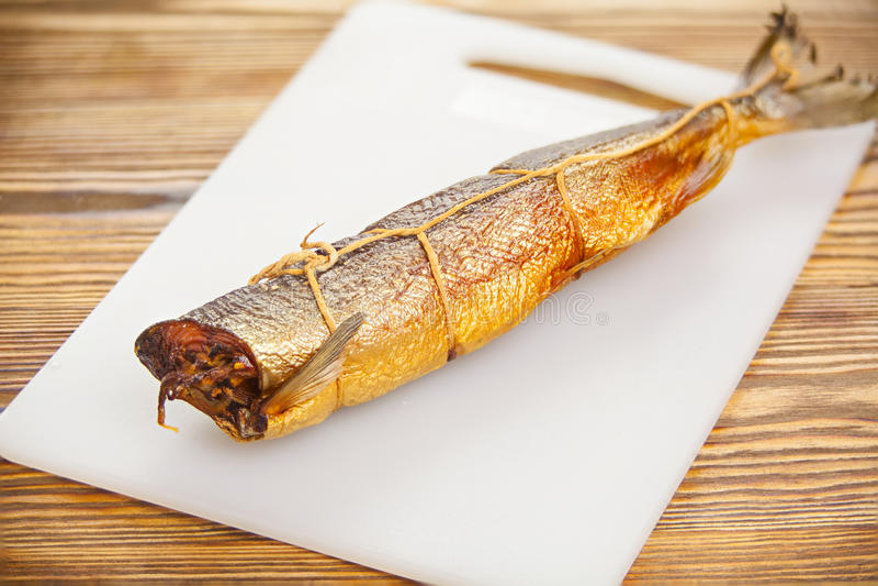 Varm rökt laxfisk på kökbräde på tabellen royaltyfri fotografi