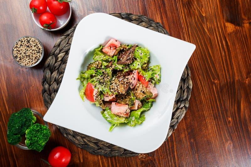 Varm sallad med feg lever, tomater, grönsallatsidor, broccoli på trätabellen fotografering för bildbyråer