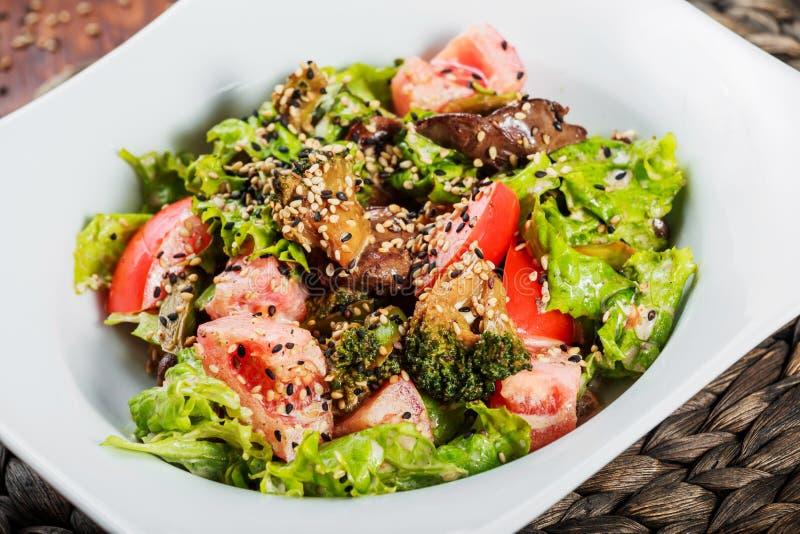 Varm sallad med feg lever, tomater, grönsallatsidor, broccoli på trätabellen sund mat arkivfoto