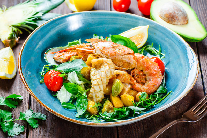 Varm sallad med skaldjur, langoustine, musslor, räkor, tioarmad bläckfisk, kammusslor, mango, ananas, avokado, arugula på träbakg royaltyfri fotografi