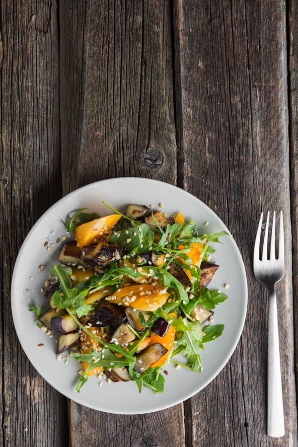 Varm sallad med stekt aubergine, arugula, körsbärsröda tomater, royaltyfri foto
