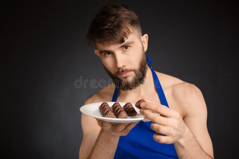 Varm sexig naken stilig man med choklader, chokladgodisar Le bärande mörker för naken stilig man - blått förkläde som rymmer en v arkivfoton