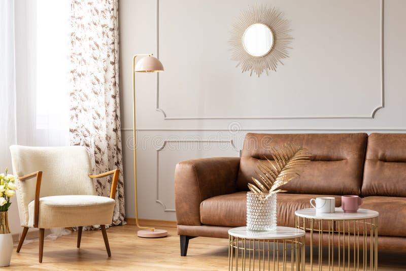 Varm vardagsruminre med tabeller för en lädersoffa, fåtölj-, lamp- och kaffemed en vas arkivfoton