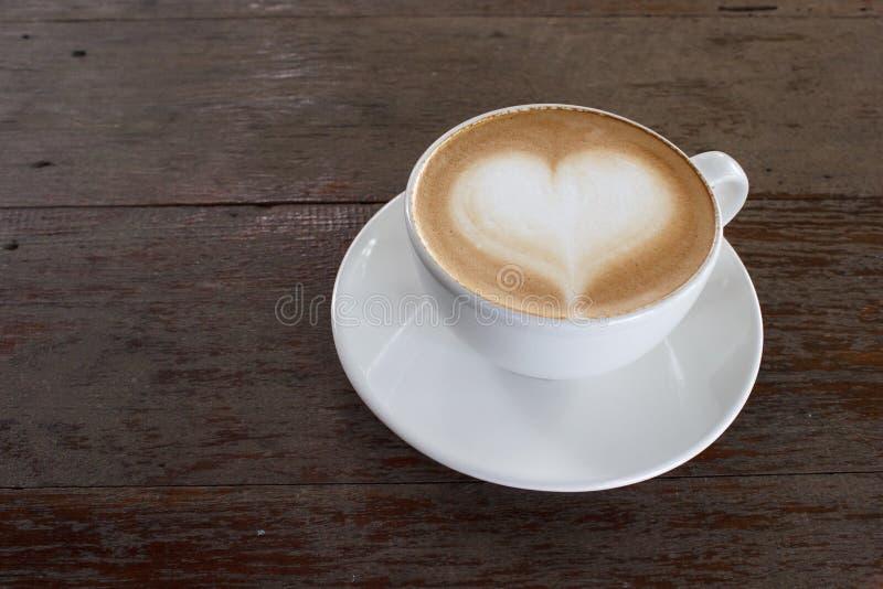 Varm vit kopp kaffe med hjärtaform på den wood tabellen med kopieringsutrymme royaltyfri bild