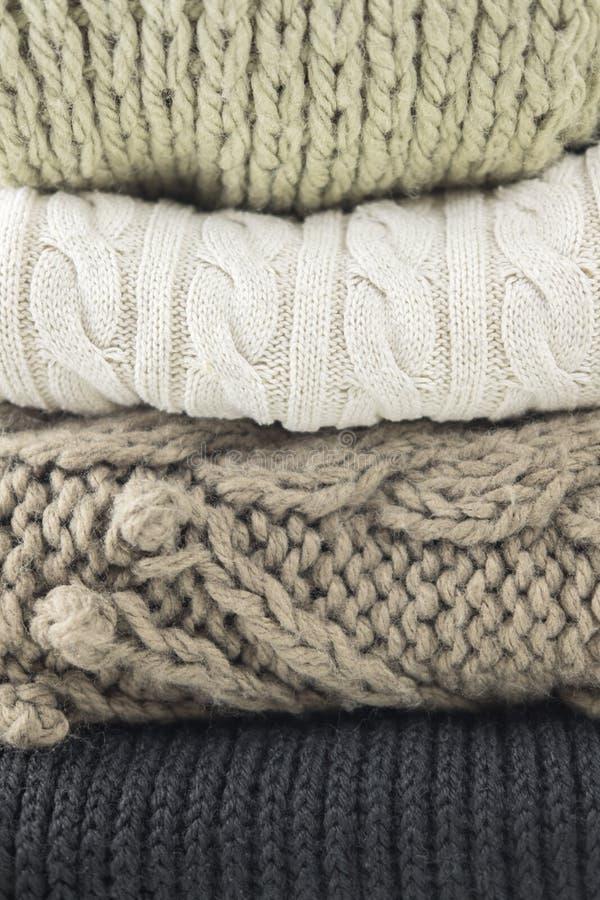 Varm woolen stucken vinter- och höstkläder, vikt i en hög Tröjor scarves Närbild royaltyfria foton