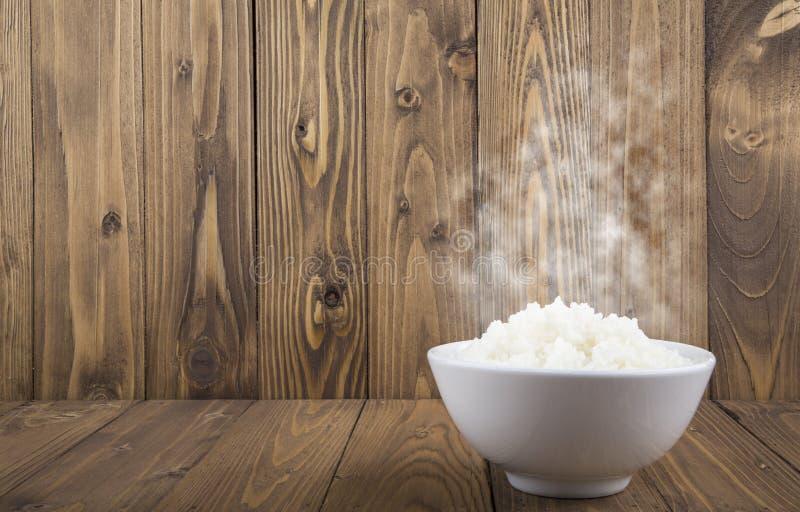 Varma ångade ris i en vit bunke på träbakgrund arkivfoton
