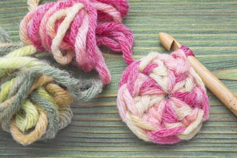Varma bollar för rosa färg- och gräsplanvintergarn för att sticka och virkning på tabellen Closeupfoto av virkningdoilyen Virknin royaltyfria foton