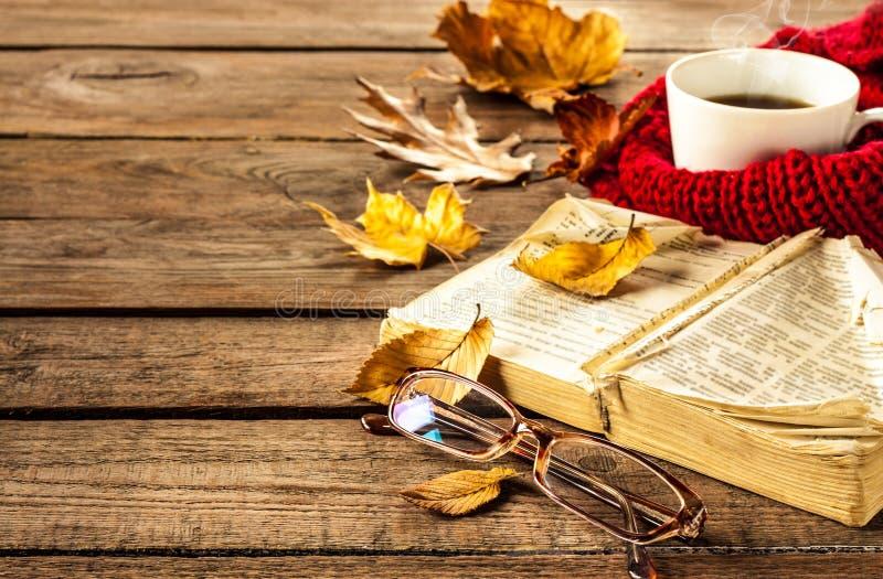 Varma kaffe, bok, exponeringsglas och höstsidor på wood bakgrund royaltyfria foton