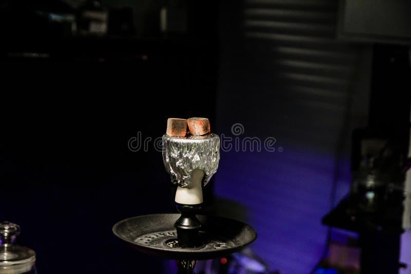 Varma kol för vattenpipa för att röka shisha och fritid i östlig modellbakgrund Bunke med tobak och kol Vattenpipatapet royaltyfri fotografi