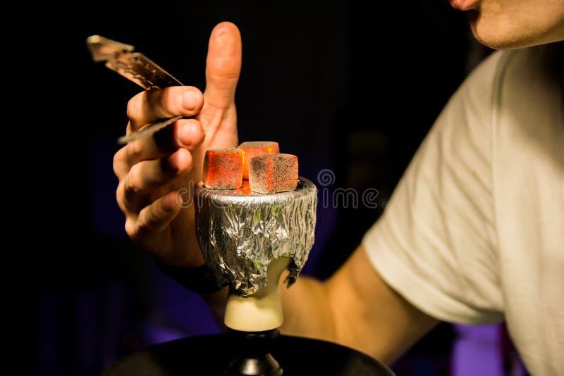 Varma kol för vattenpipa för att röka shisha och fritid i östlig modellbakgrund Bunke med tobak och kol Vattenpipatapet royaltyfri bild