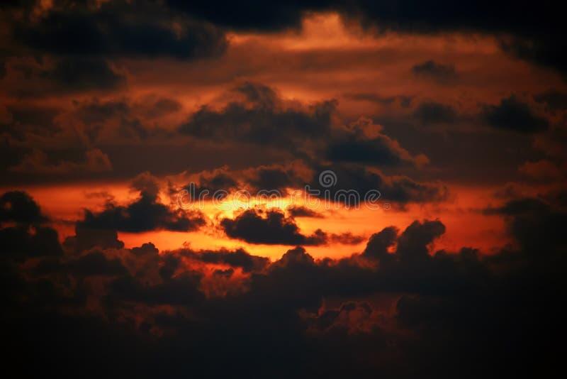 Varma orange röd solnedgånghimmel och molnmodellbilder Flammande solnedgång med ljus bortgång till och med de mörka molnen Landsk arkivfoton