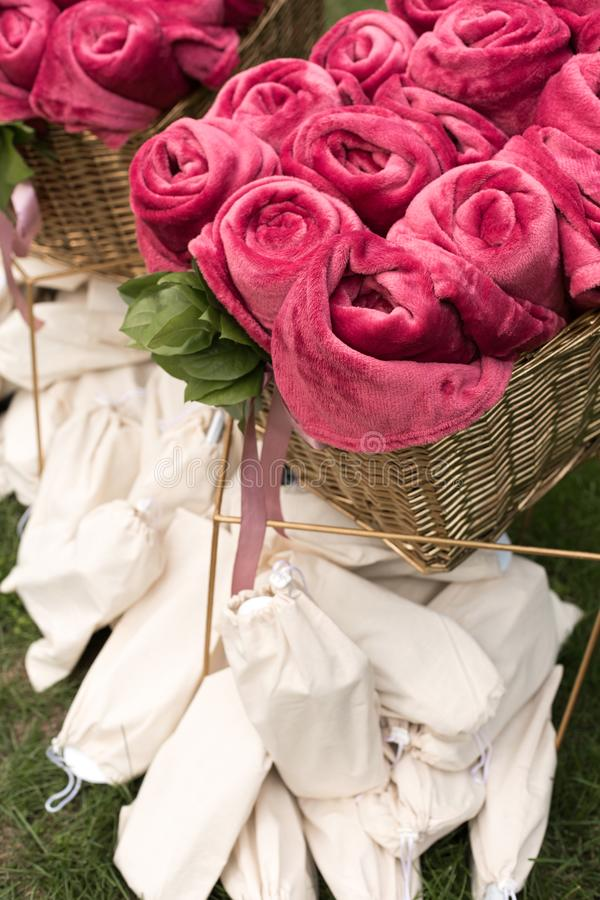 Varma rosa filtar som är hoprullade i form av rosor i en stor korg för gäster på ett utomhus- gifta sig parti Vit individuell dan arkivbild