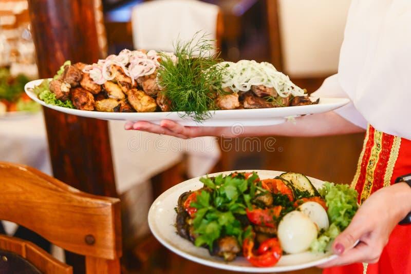 Varma steknålar med lökar på den vita plattan, grillat kött Kebabrestaurang Att att tjäna som kebaberna Caucasian kök royaltyfri foto