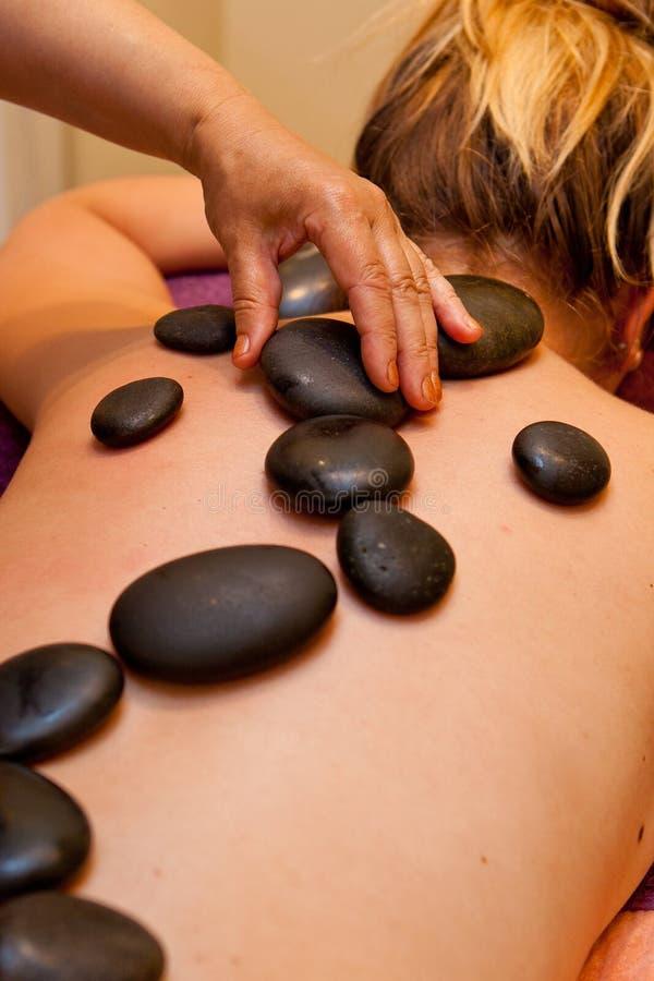 Varma stenar fodrade på den unga kvinnans baksida för massage fotografering för bildbyråer