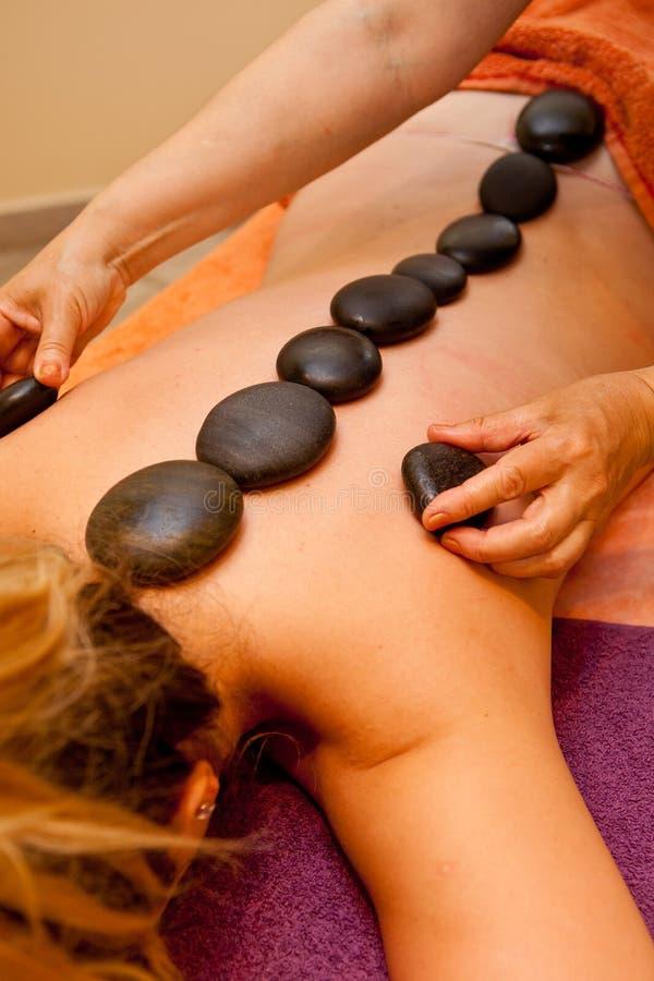 Varma stenar fodrade på den unga kvinnans baksida för massage royaltyfria bilder