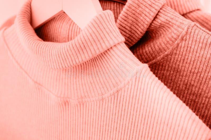 Varma tröjor hänger på enfärgad laghängare royaltyfria foton