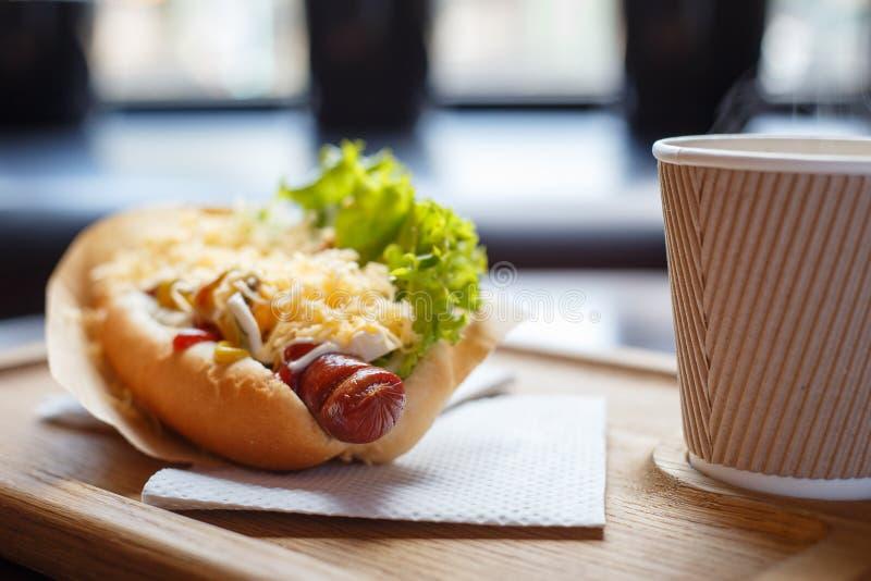Varmkorv med sallad och koppen kaffe på tabellen royaltyfri bild