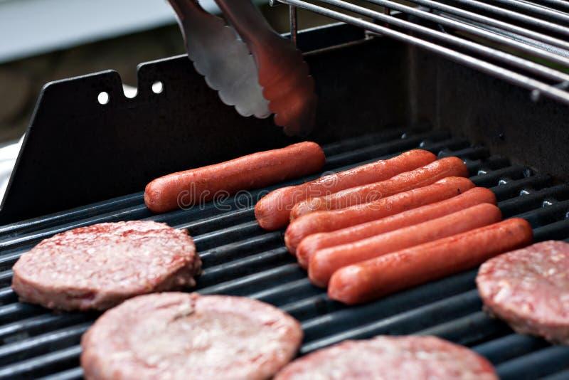 Varmkorvar och hamburgare på gallret royaltyfri foto