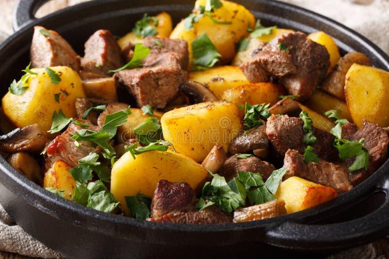 Varmrätten av stekt griskött med potatisar och champinjonnärbild i pannan horisontal royaltyfri foto
