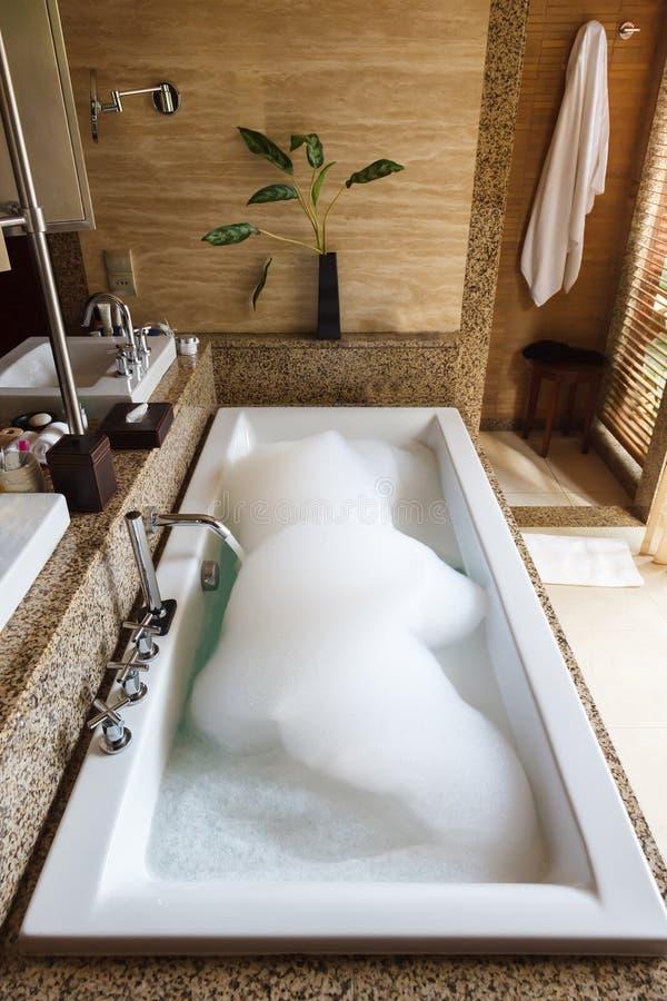 Varmt avslappnande bad med blom- arom och skum royaltyfria foton