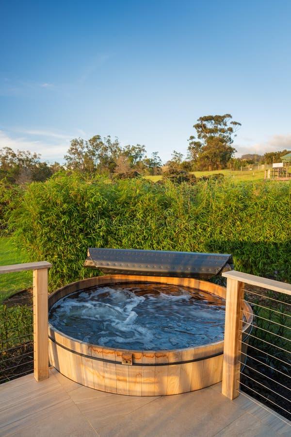 Varmt bada bubbelpoolen förutom ett modernt hus arkivbilder