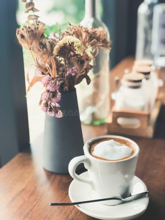 Varmt cappuccinokaffe i den vita koppen på den wood tabellen med blomman arkivbild