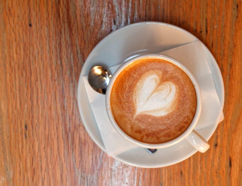 Varmt cappuccinokaffe med hjärta formad fradga arkivbild