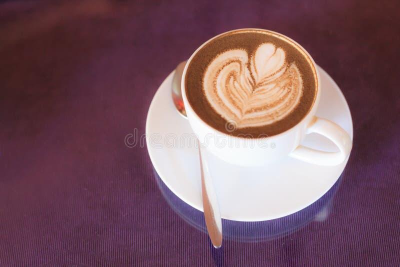 Varmt cappuccinokaffe som dekoreras med att blomma blommafradgakonst på ångat, mjölkar skum i den vita koppen på trätabellba royaltyfria bilder