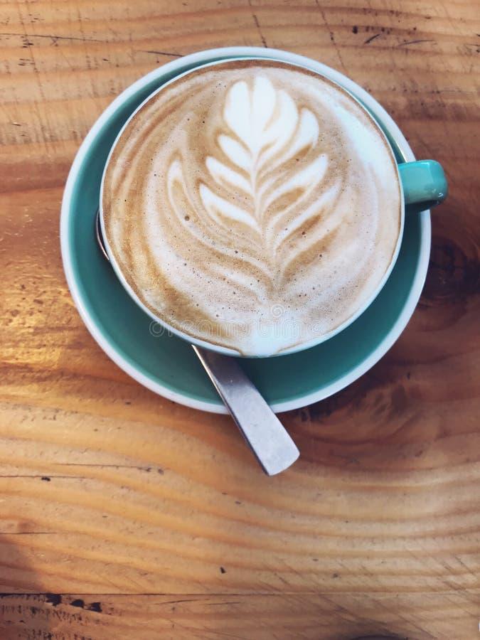 Varmt cappuccinokaffe som dekoreras med trädsidor på Milk Latte, skummar fradgakonst i blått rånar koppen på lantlig trätabellbak royaltyfria foton