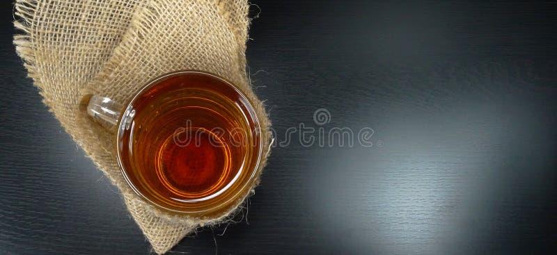 Varmt exponeringsglas för tekopp på en vinterdag med säckväv/hessians på en svart bakgrundstetid! arkivfoton