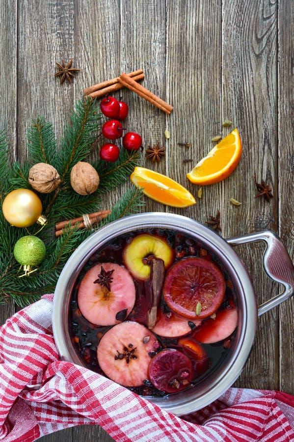 Varmt funderat vin i en stor panna på en trätabell Doftande traditionell vinterdrink royaltyfria foton