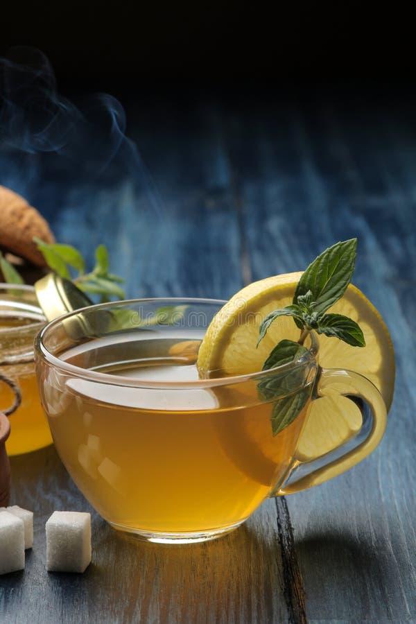 Varmt grönt te med kanel, mintkaramellen och citronen bredvid socker på en blå trätabell arkivfoton